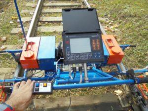 Рабочий проверяет железнодорожные пути дефектоскопом.