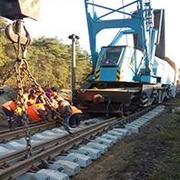 Рабочие с помощью подъёмного крана ремонтируют железнодорожный путь