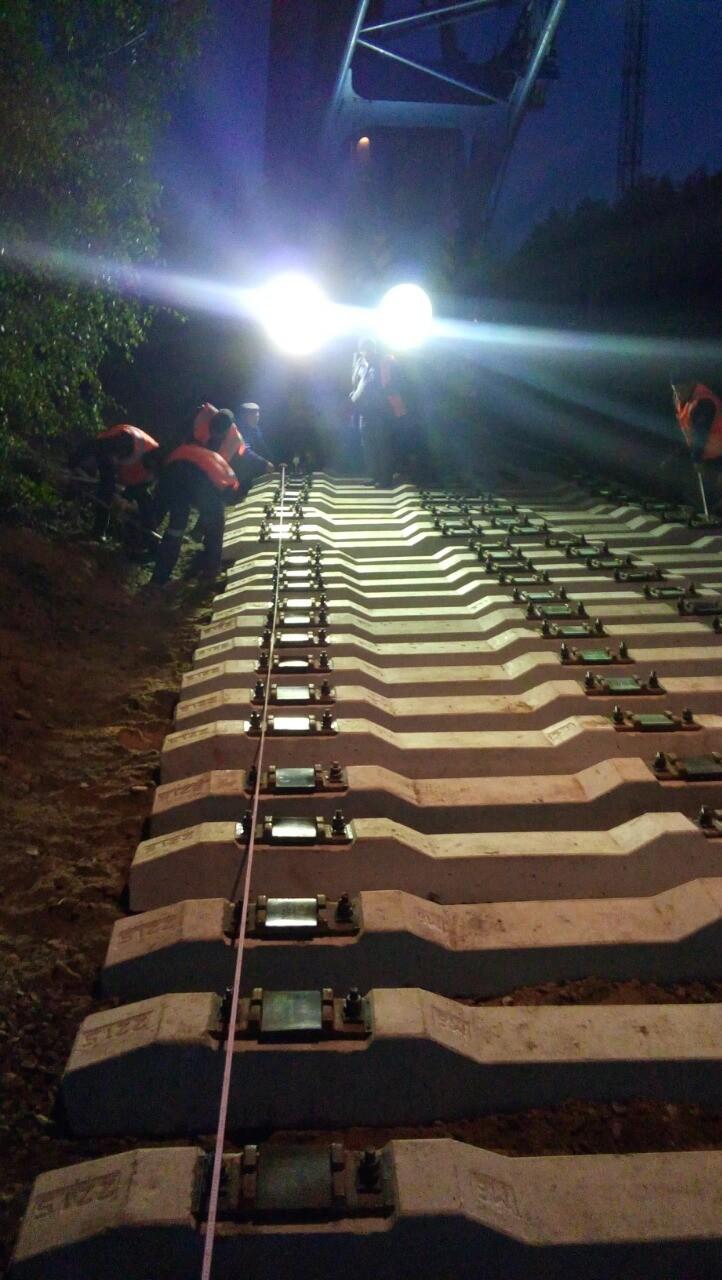 Рабочие в тёмное время суток укладывают шпалы