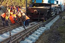 Рабочие в жилетах с помощью подъёмного крана ремонтируют жд путь