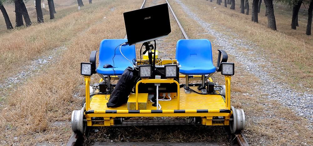 Дефектоскоп жёлтого цвета на железнодорожных путях. Рельсовая дефектоскопия