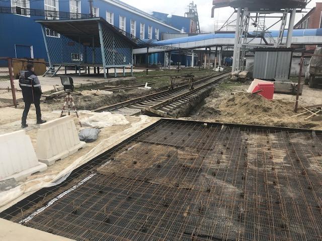Рабочий, сетка из арматуры на земле, жд путь на объекте ГК «АСБ» ООО «Кристалл»